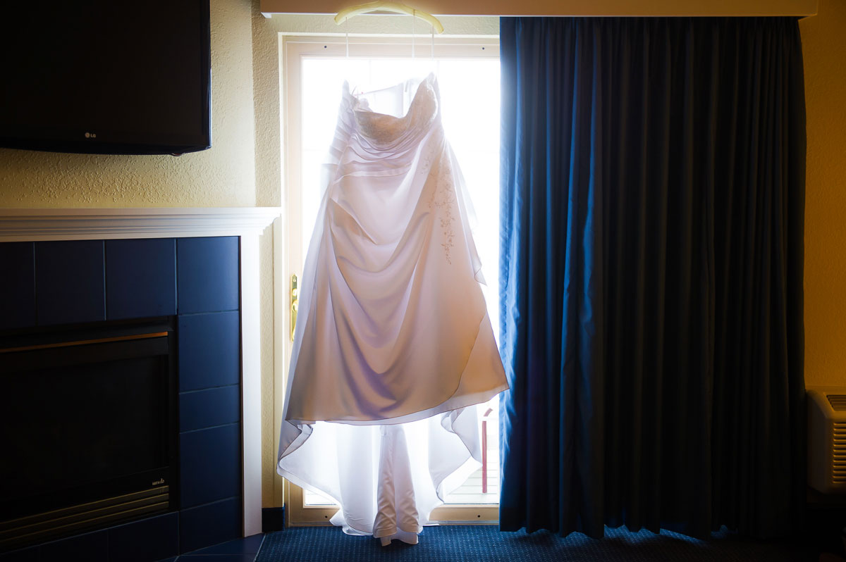 Wedding dress hanging in window at Blue Harbor Resort.