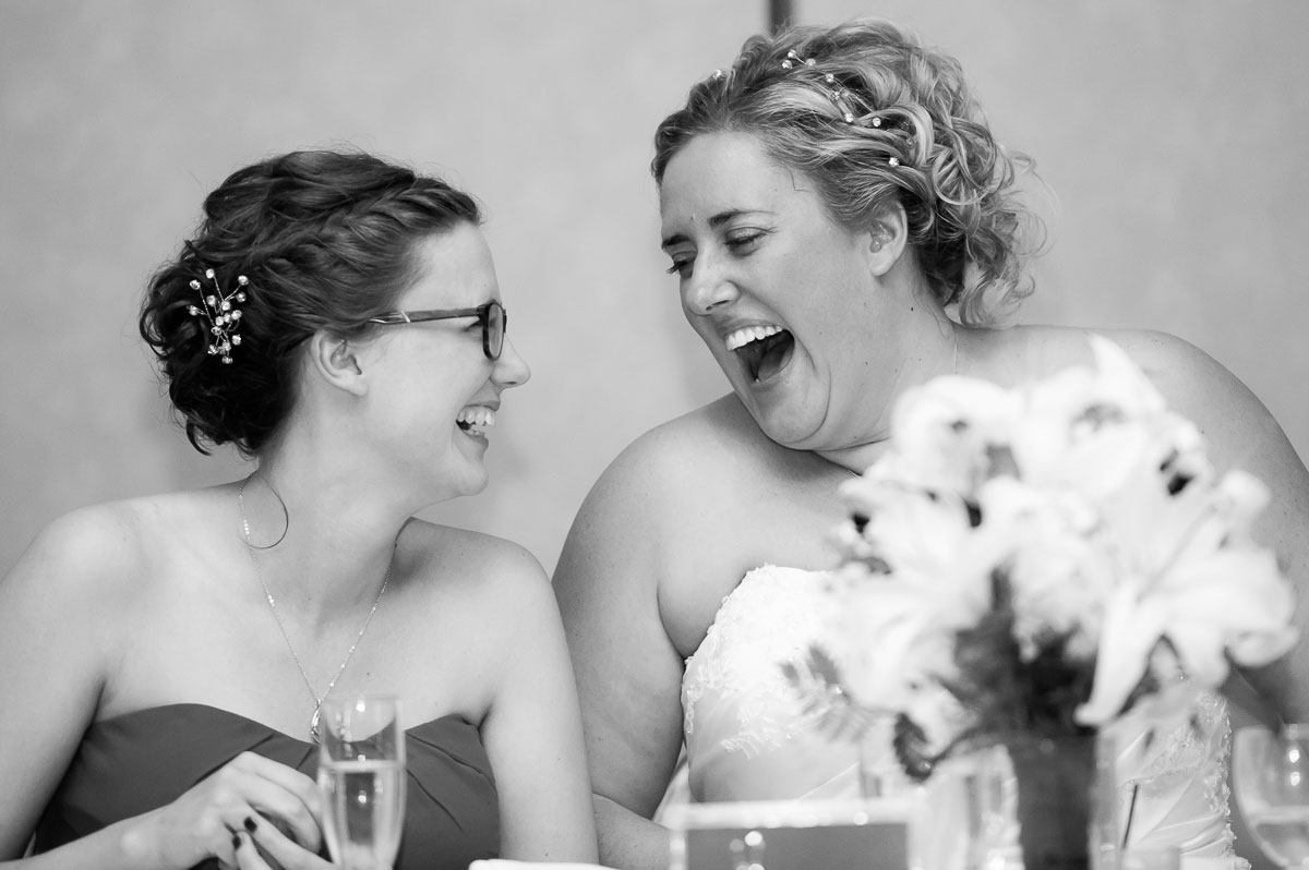 The bride and maid-of-honor share a laugh during a wedding reception at Blue Harbor Resort.