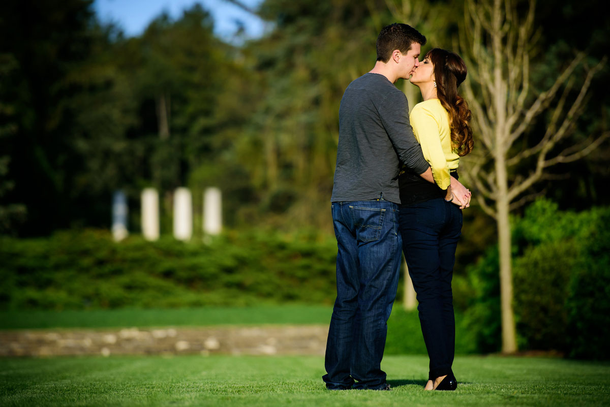 A couple kisses duringtheir engagement session at the Morton Arboretum in Lisle, IL.