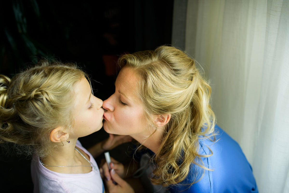Mother and daughter kiss while getting ready before a wedding at the Trump Tower Chicago.