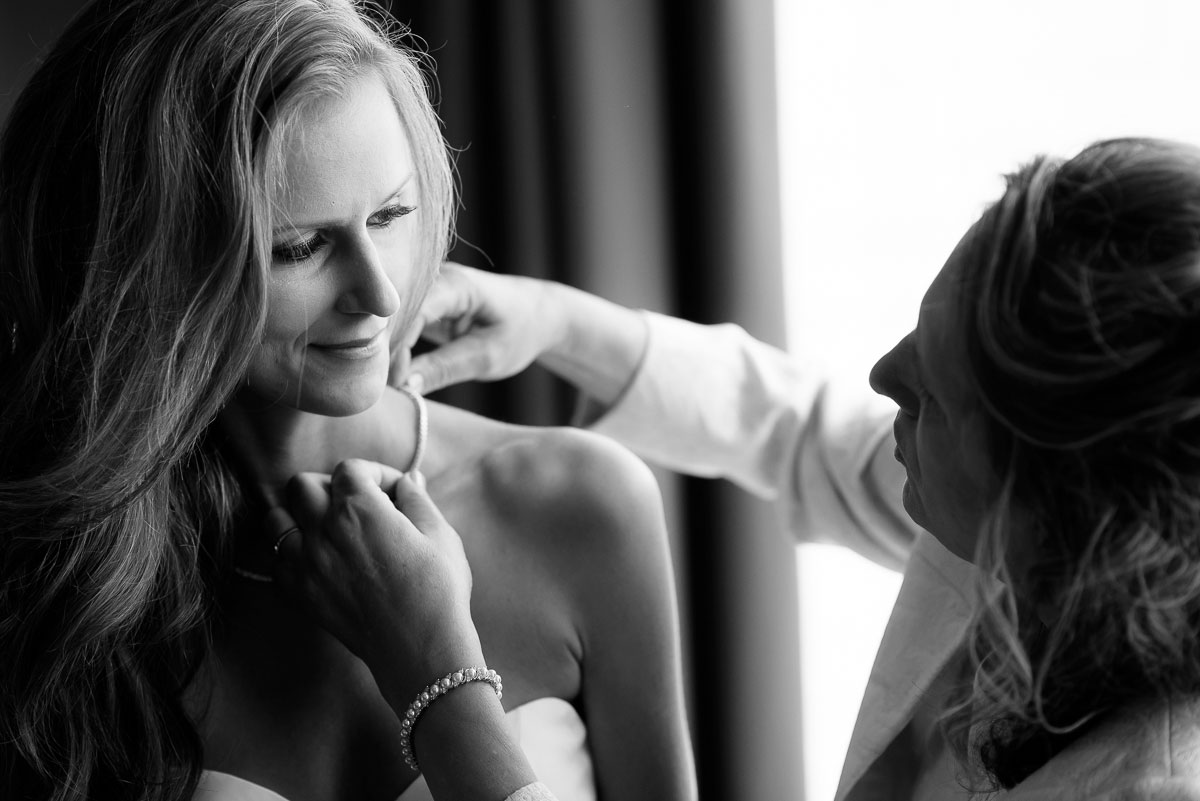 Mother-of-the-bride adjusts her daughters jewelry on her wedding day at the Trump Tower Chicago.