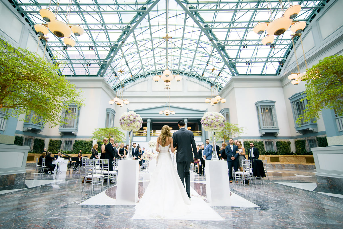 Bride walks down the aisle during a wedding at the Winter Garden in the Harold Washington Library Chicago.