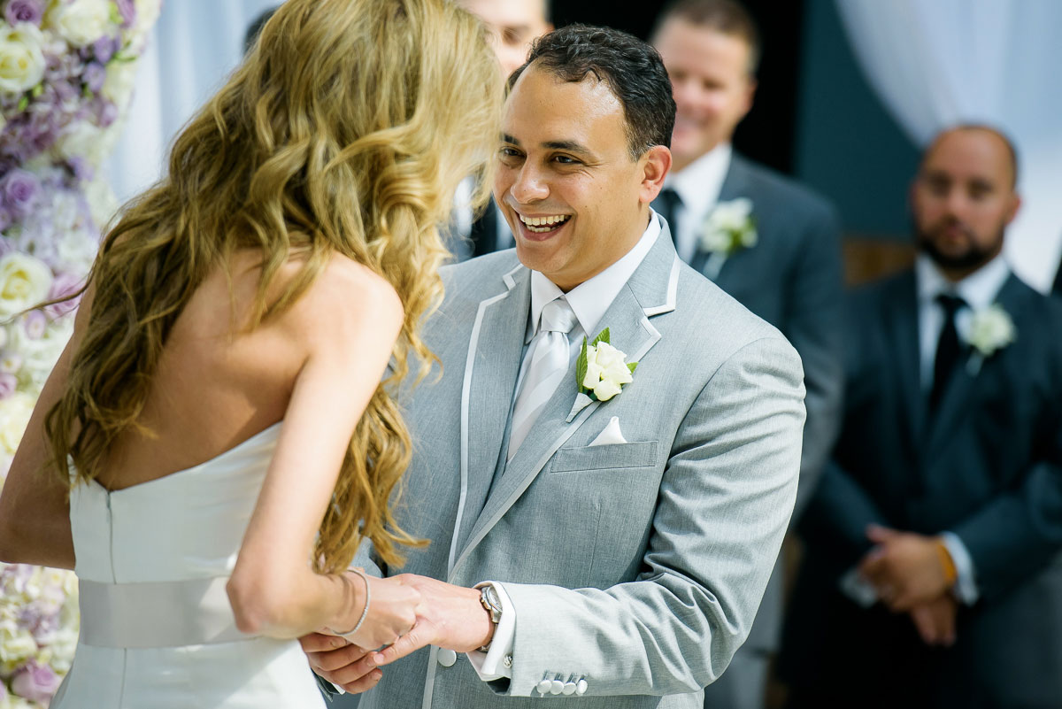 Bride and groom share a laugh during their wedding ceremony in the Winter Garden at the Harold Washington Library Chicago.