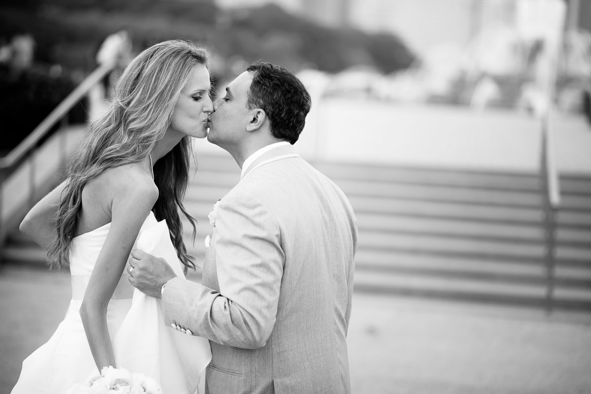Bride and groom share a kiss during their wedding photos at the Tiffany Gardens in Chicago.