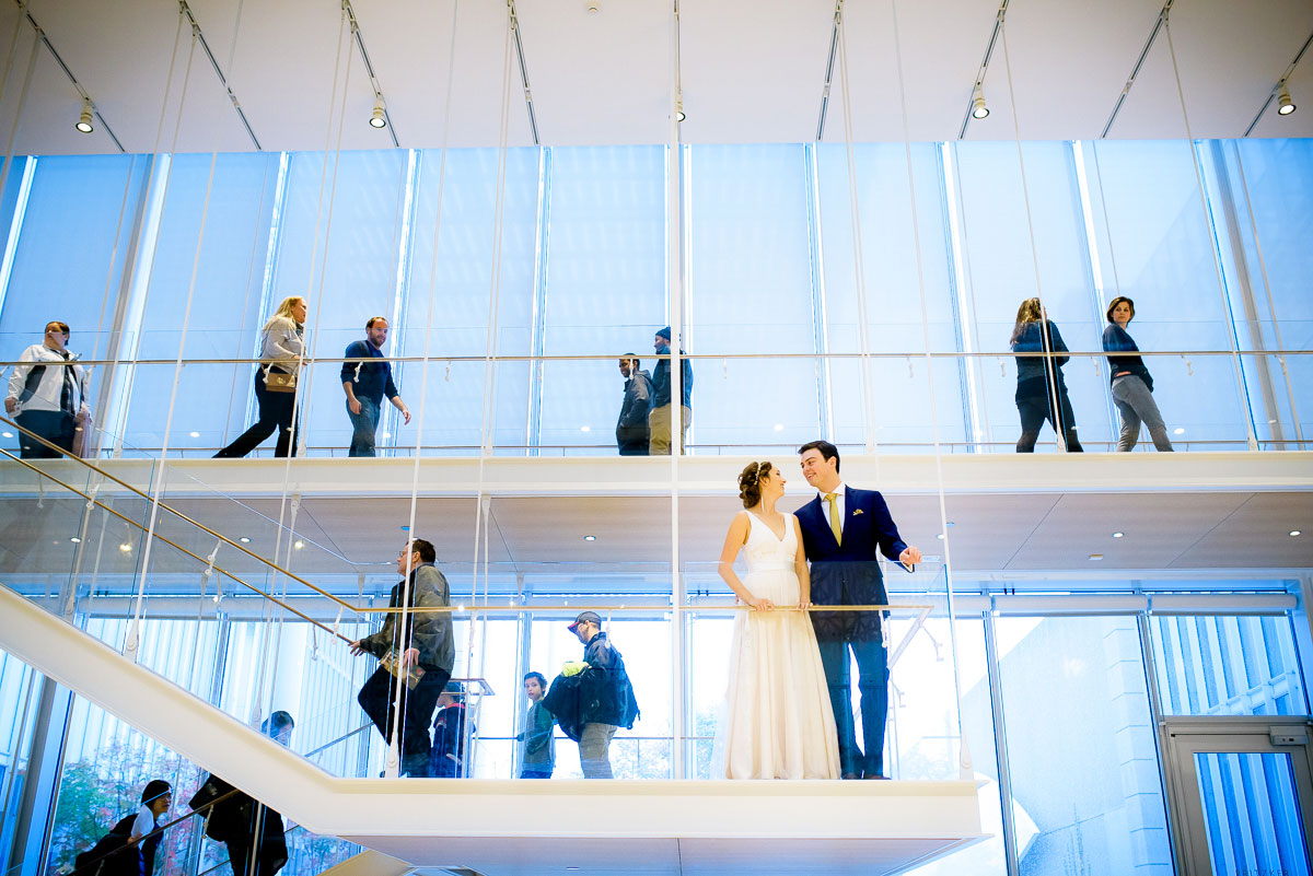 Bride & groom amongst the crowd in the Modern Wing of the Art Institute of Chicago on their wedding day.