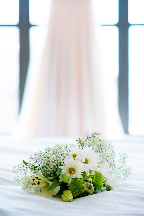 Bridal bouquet and wedding dress detail photo at the James Hotel.