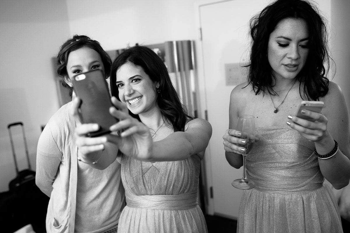 Bridesmaids take selfies on the wedding day at the James Hotel.