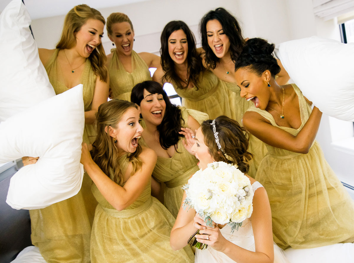 Fun and creative bridal party photo of a mock pillow fight on the wedding day at the James Hotel.