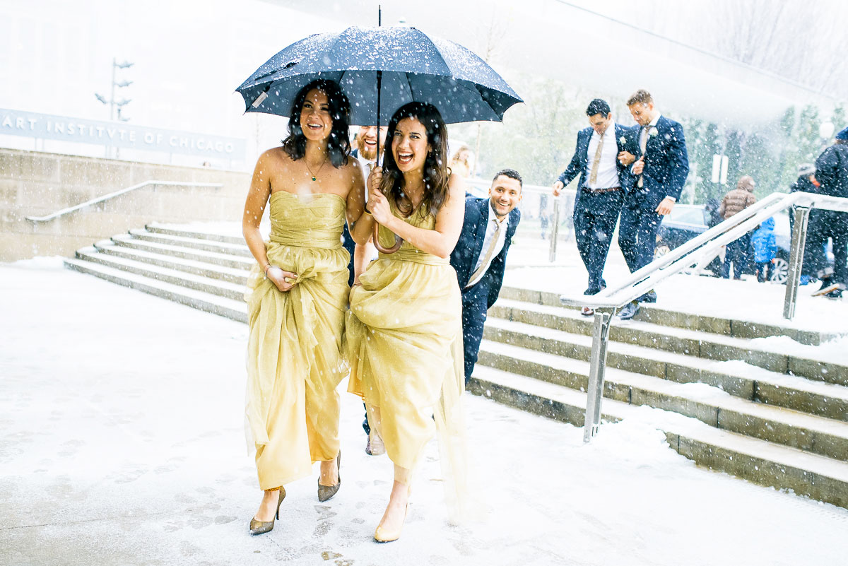 Bridal party walks through the snow to the Art Institute of Chicago for wedding photos.