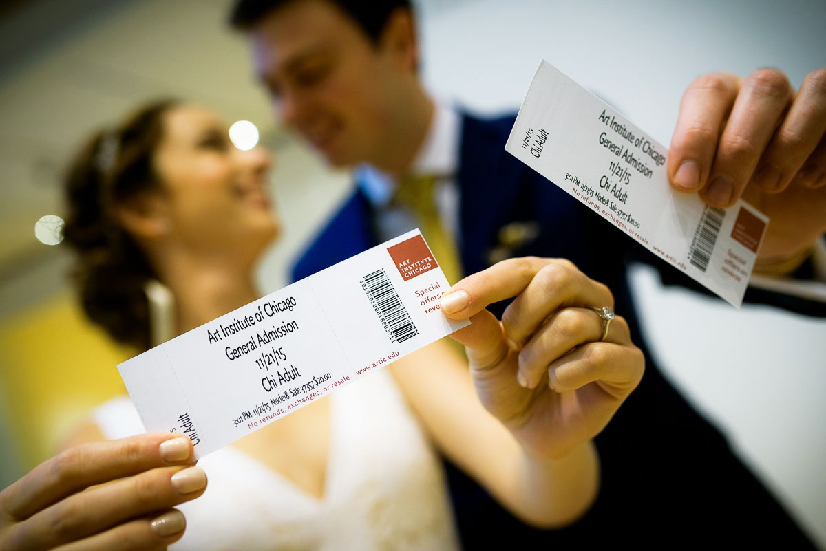 The wedding couple holds up their tickets to the Art Institute of Chicago.
