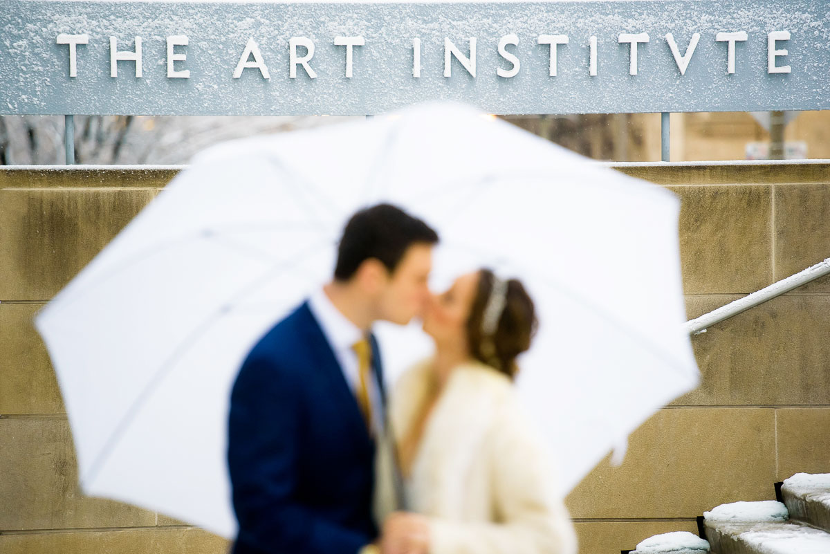 Bride & groom kiss on their wedding day outside the Art Institute of Chicago.