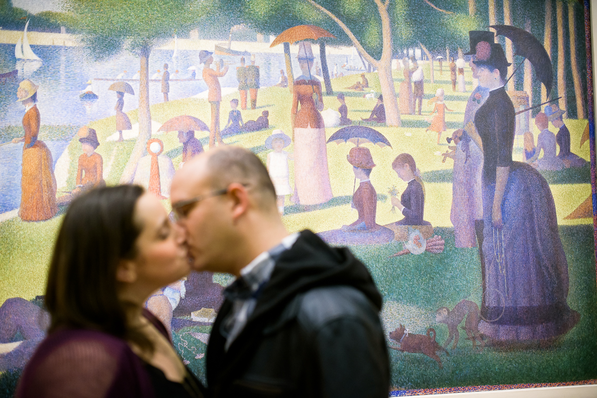"Couple kisses in front of ""A Sunday Afternoon on the Island of La Grand Jatte"" at the Art Institute of Chicago during their engagement session."