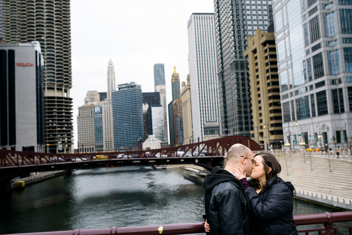 A couple kisses on the LaSalle Street Bridge during their Chicago engagement session.
