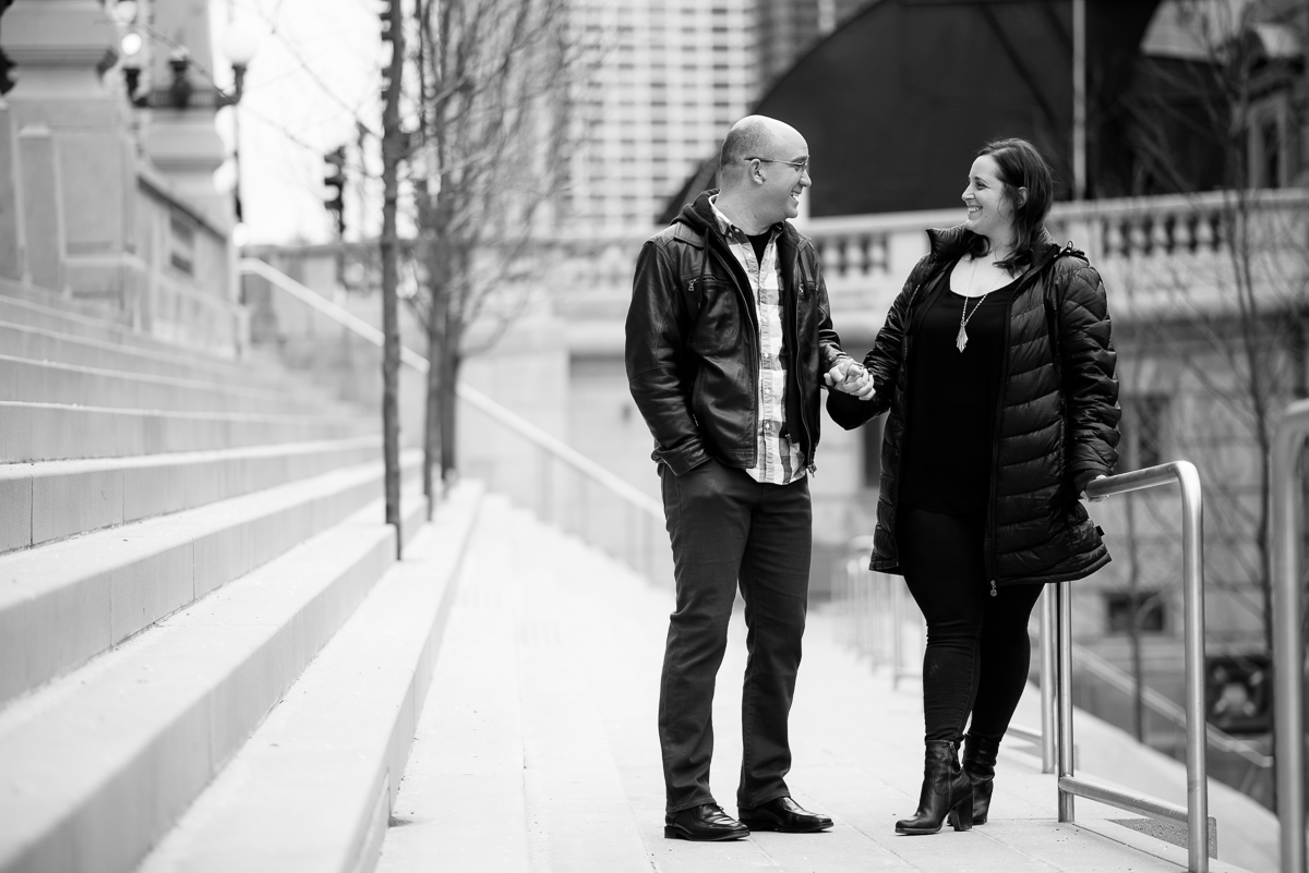 A couple shares a laugh along the Riverwalk during their Chicago engagement session.