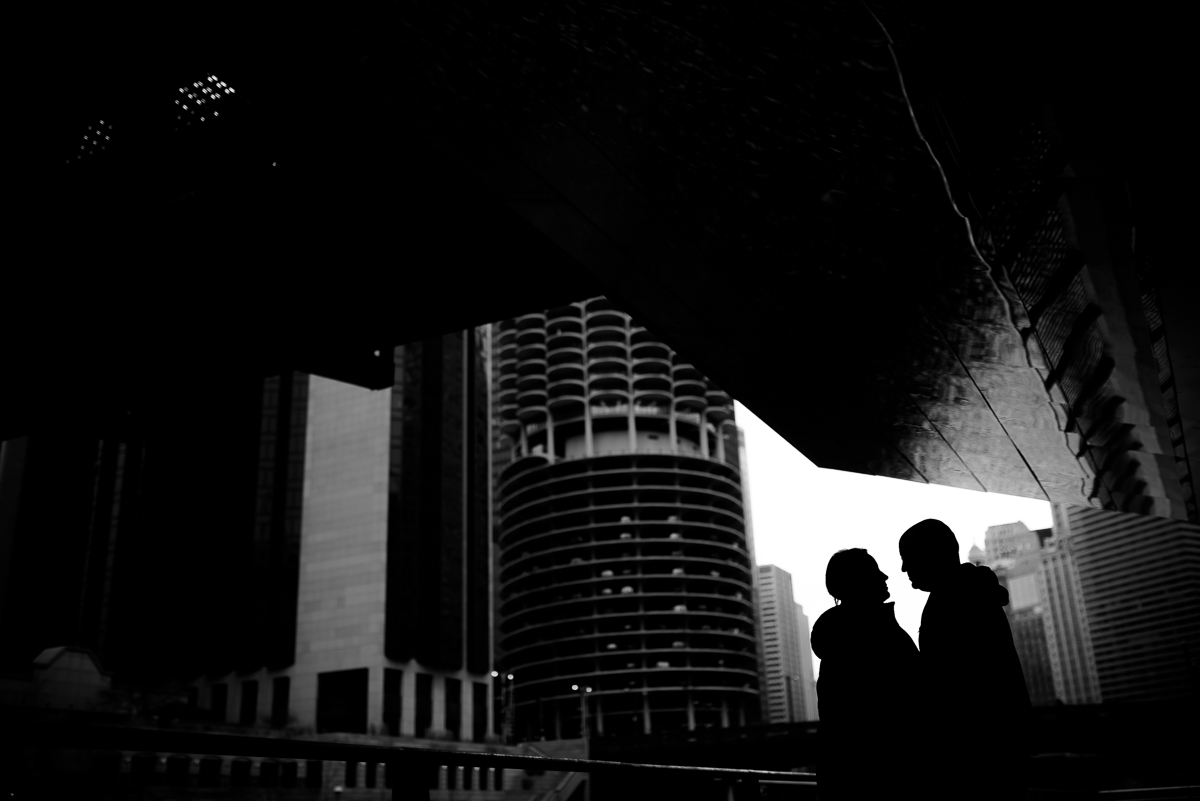 A couple is silhouetted along the Riverwalk near Marina Tower during their Chicago engagement session.