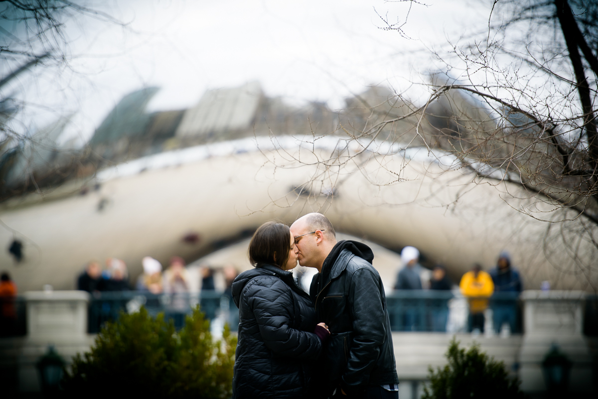 Bride & groom kiss with the Bean in the distance during their Chicago engagement session.