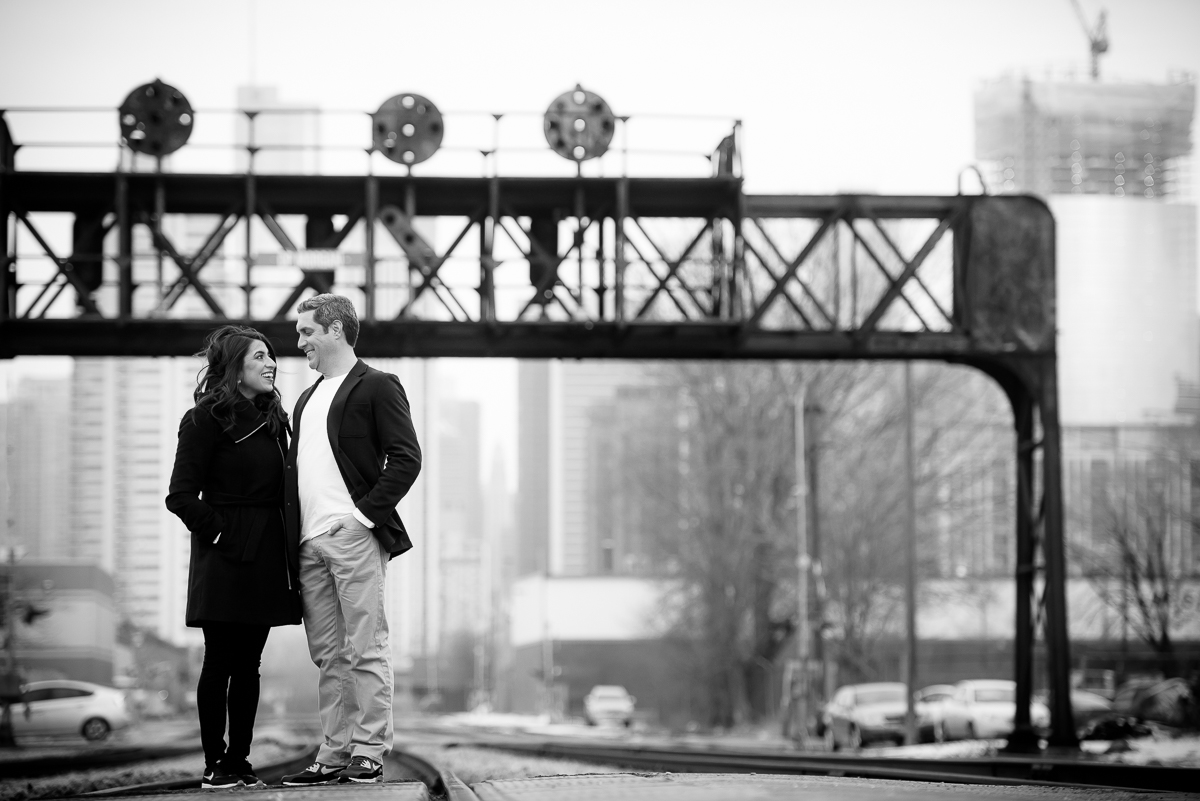 The couple stands along the train tracks in the Fulton Market area during their Chicago engagement session.