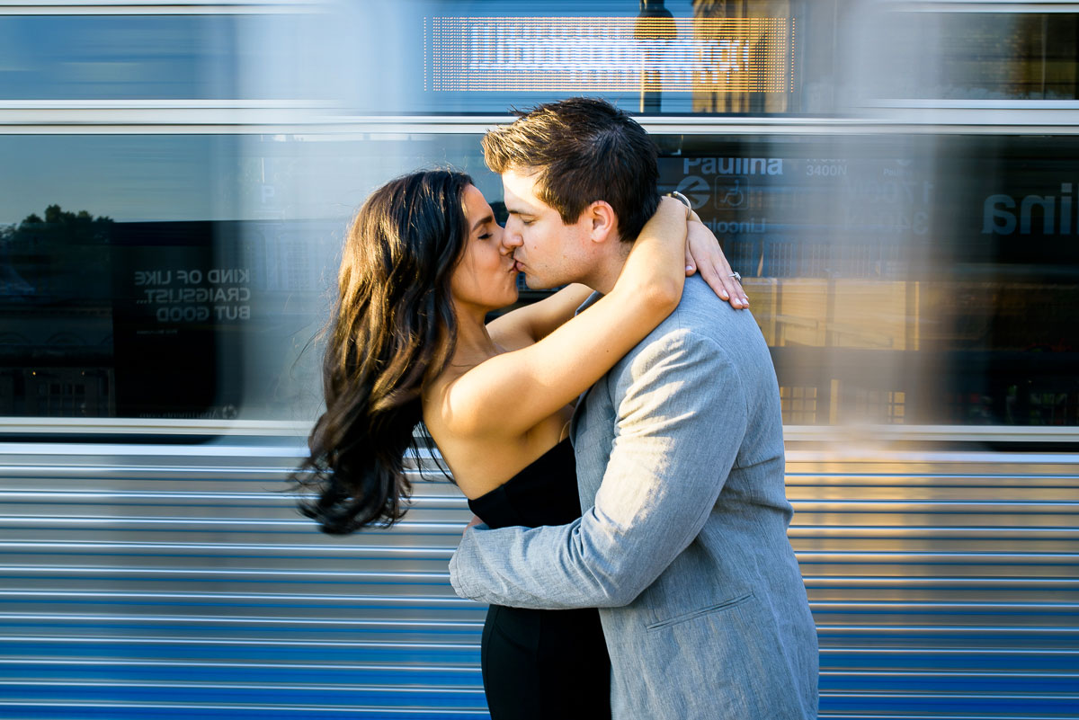 The el train flies past the couple during their Chicago engagement session.