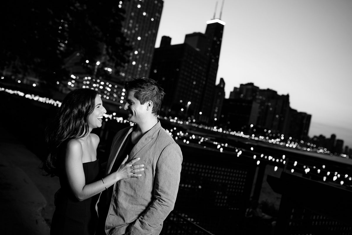 The couple shares a laugh during their Chicago engagement session at Ohio Street Beach at sunset.