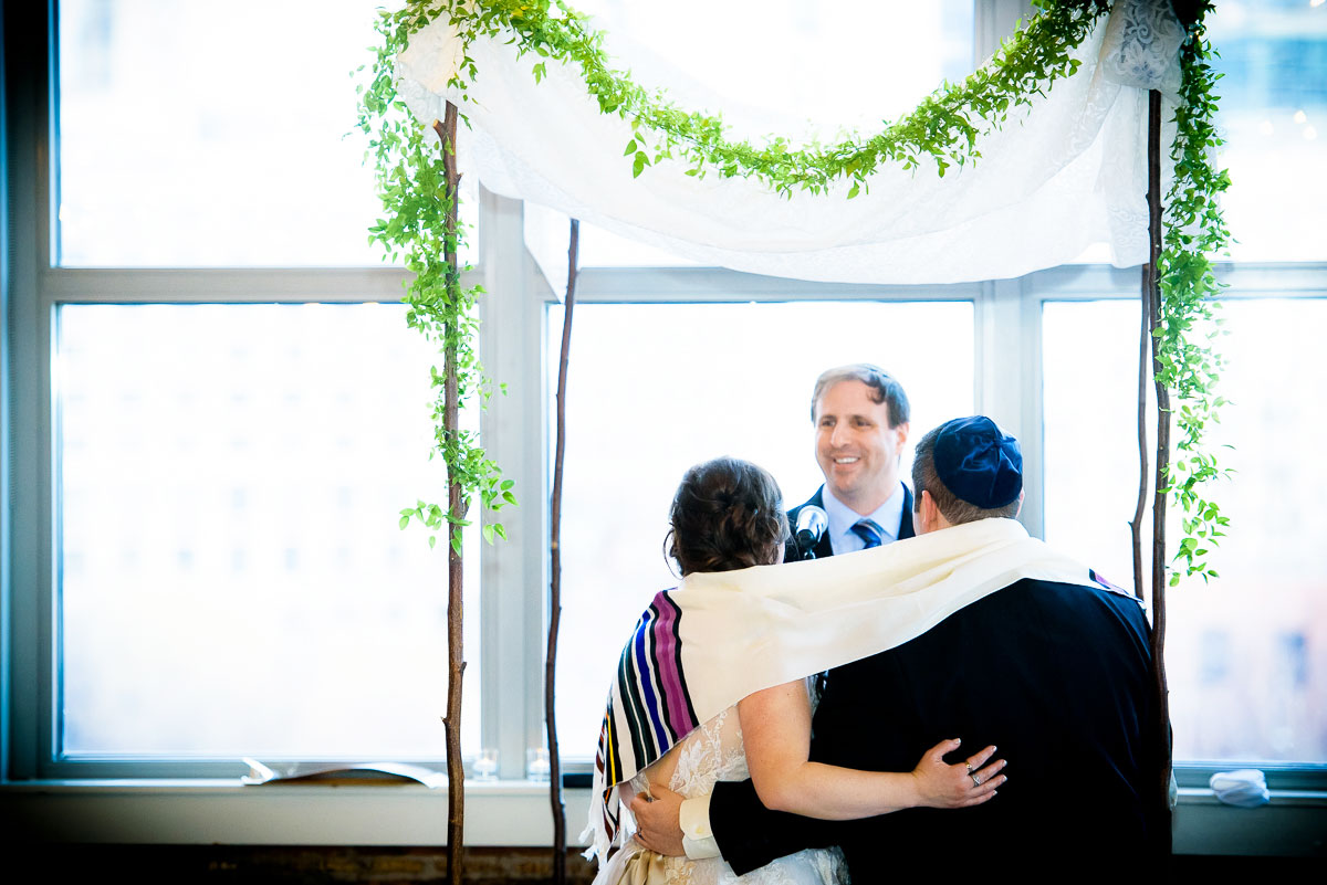 Bride & groom embrace under the huppah during their wedding at Kendall College Chicago.