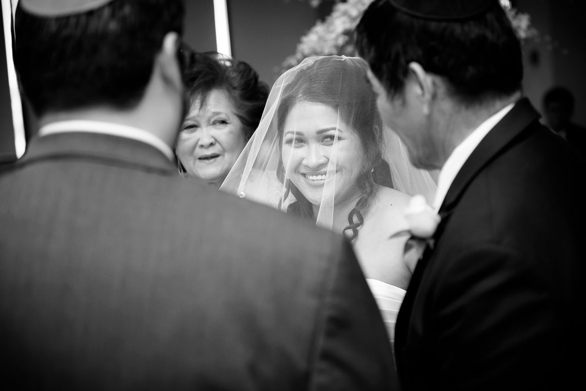 The bride smiles as she is given away by her father during her wedding at the DoubleTree Skokie.