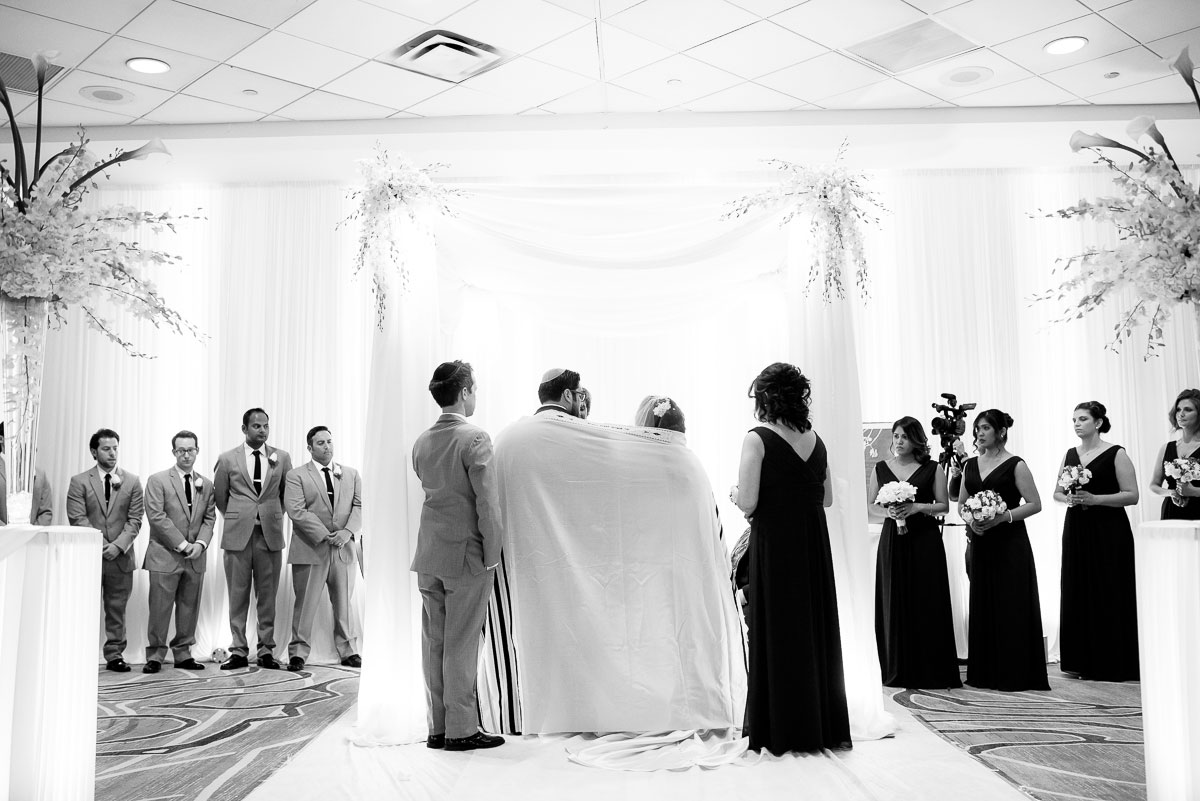 Bride & groom are wrapped in a tallis during their jewish wedding ceremony at the DoubleTree Skokie.