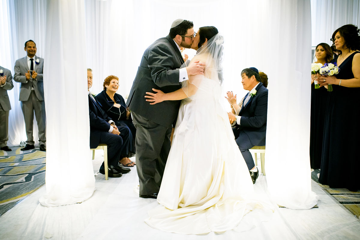 First kiss under the chuppah during a jewish wedding ceremony at the DoubleTree Skokie.