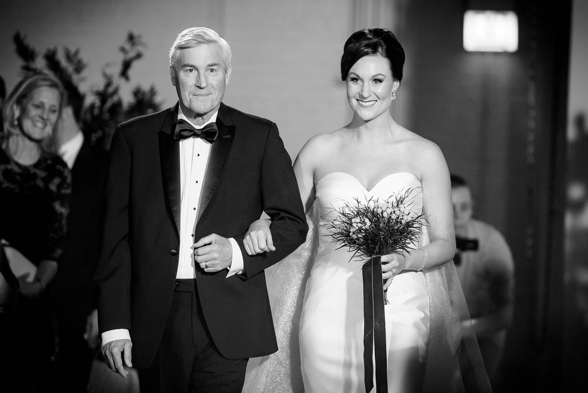 Father walks the bride down the aisle during her wedding at Moonlight Studios Chicago.