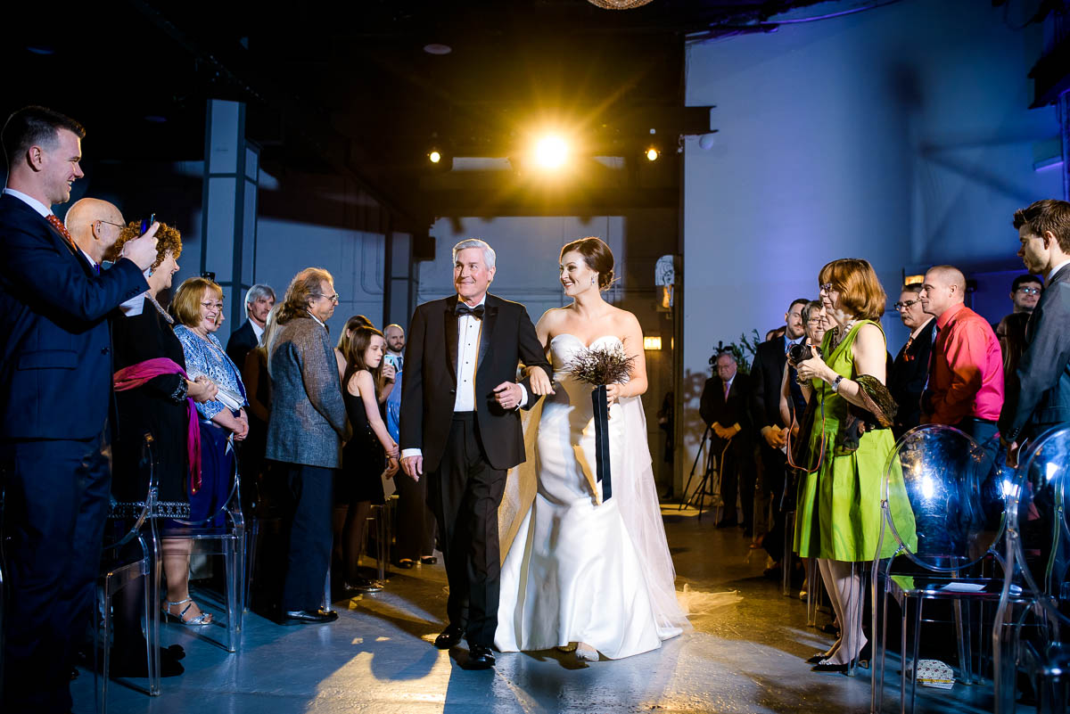 Father and bride walk down the aisle during her wedding at Moonlight Studios Chicago.