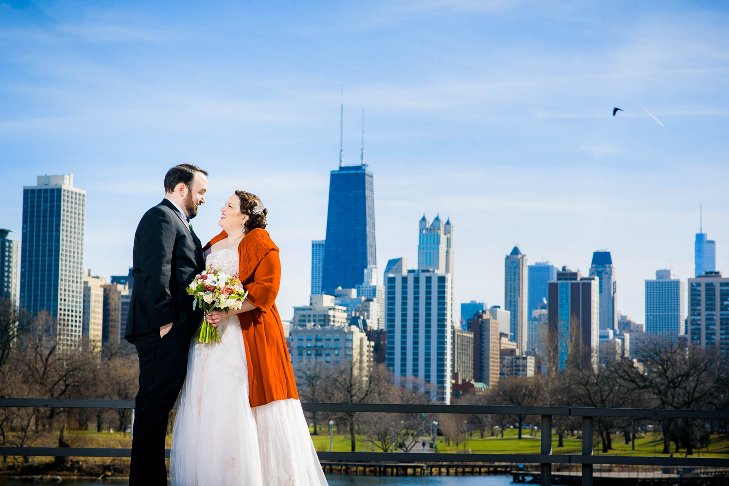 Creative portrait of bride and groom with the Chicago Skyline at Lincoln Park.