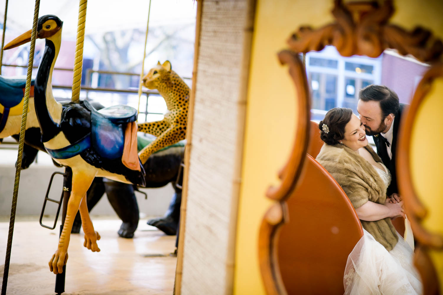Creative portrait of the bride and groom at the Lincoln Park Zoo carousel before their Cafe Brauer wedding.