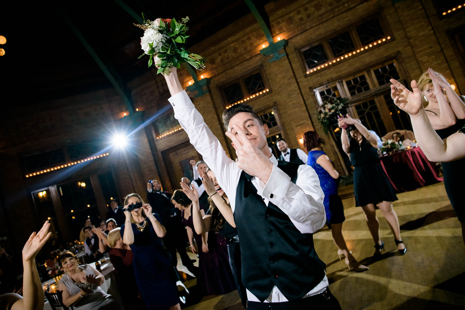 Groomsman catches the bouquet during a Cafe Brauer Chicago wedding reception.