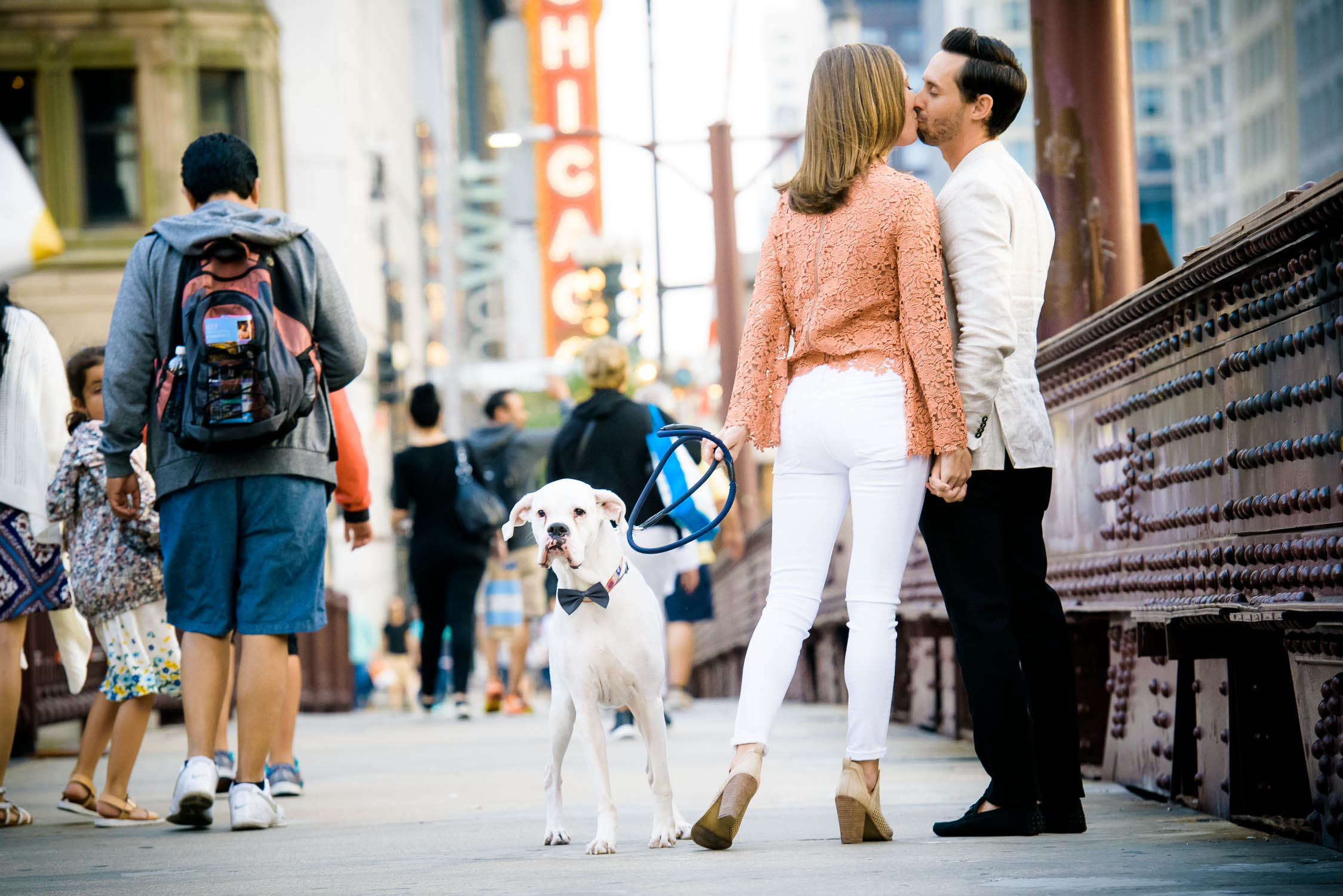 Couple embraces with their dog nearby on the State St. Bridge during their Chicago engagement session.