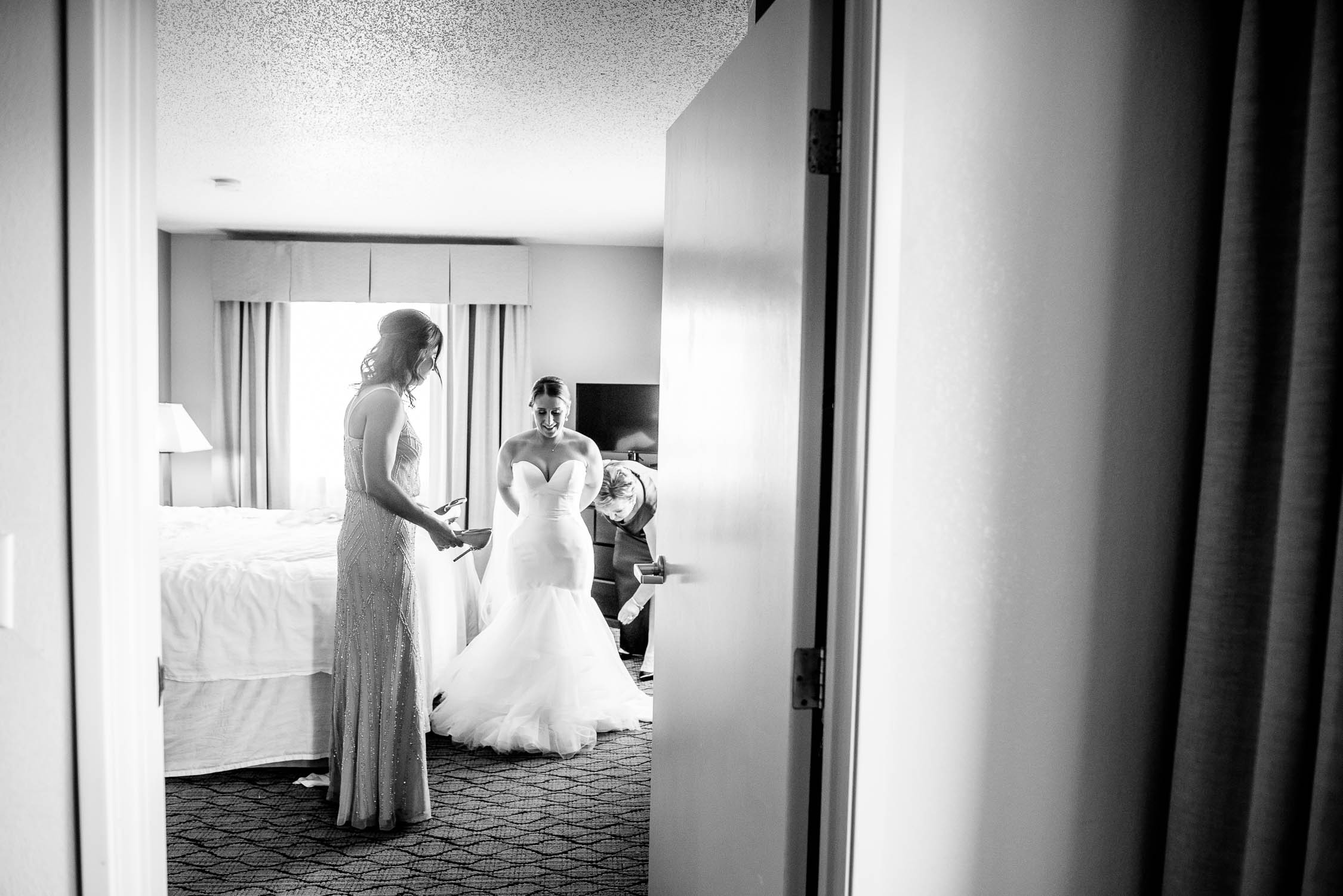 Bride puts on her dress before her wedding at Independence Grove in Libertyville.