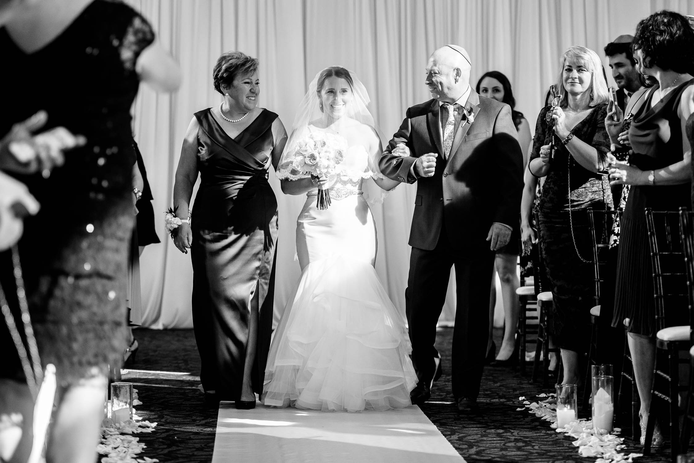 Bride and parents walk down the aisle during her wedding at Independence Grove in Libertyville.