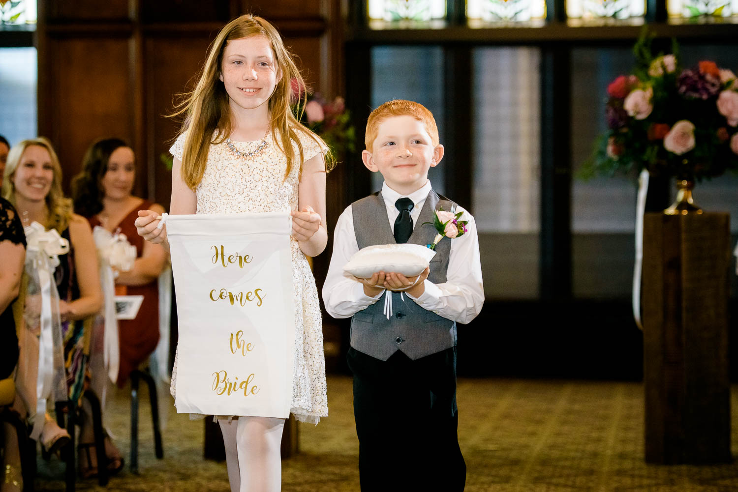 Flower girl and ringer bearer walk down the aisle during a University Club of Chicago wedding.