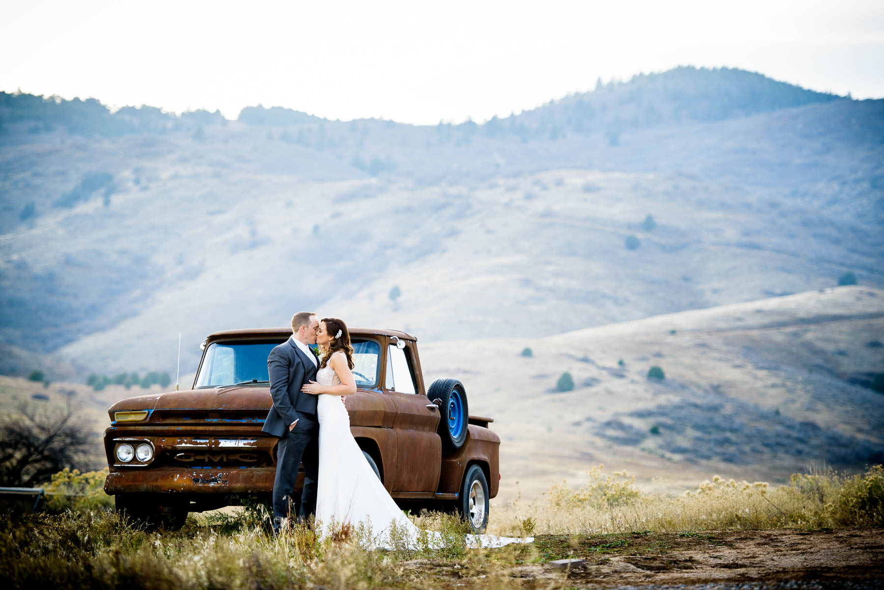 Bride & groom kiss in front of the mountains during their wedding at the Manor House in Littleton, Colorado.