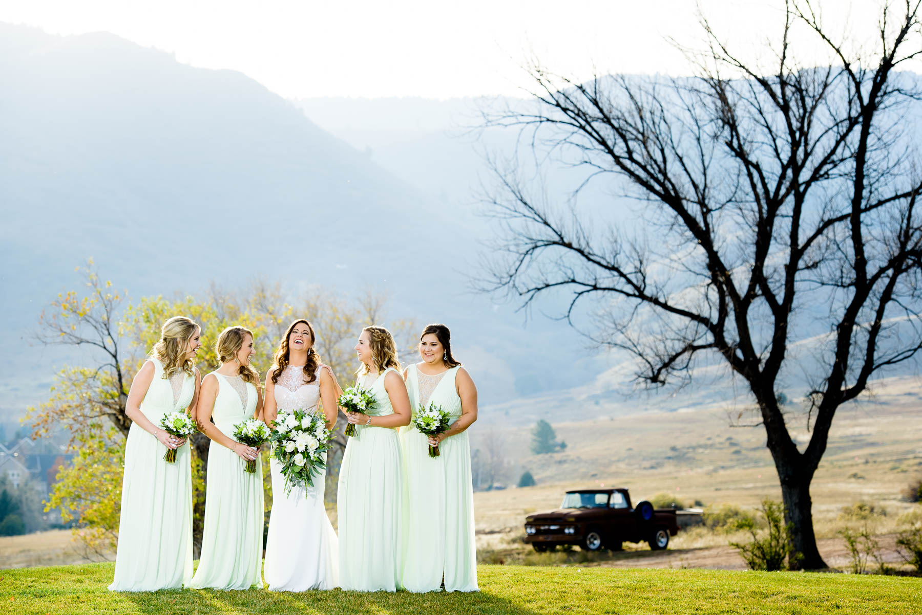 Bride and bridesmaids laugh together during a wedding at the Manor House in Littleton, Colorado.