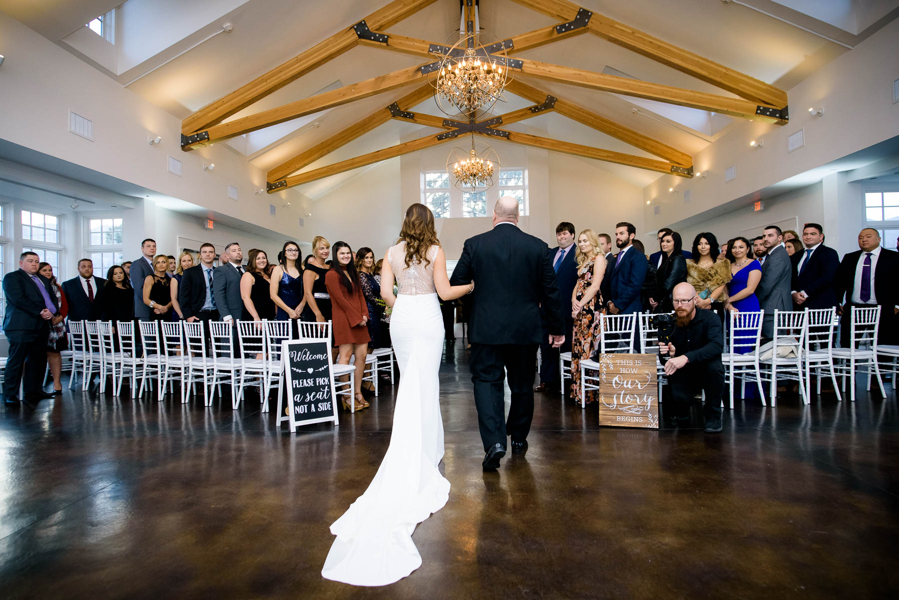 Father and bride walk down the aisle during a wedding ceremony at the Manor House in Littleton, Colorado.