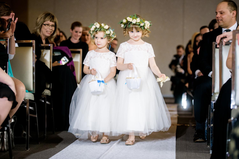 Flower girls walk down the aisle during a Thompson Chicago wedding.