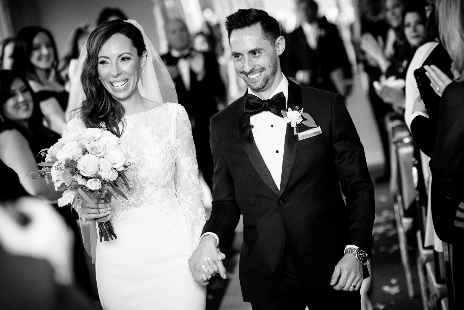 Bride and groom smile as they leave their wedding ceremony at the Thompson Chicago.