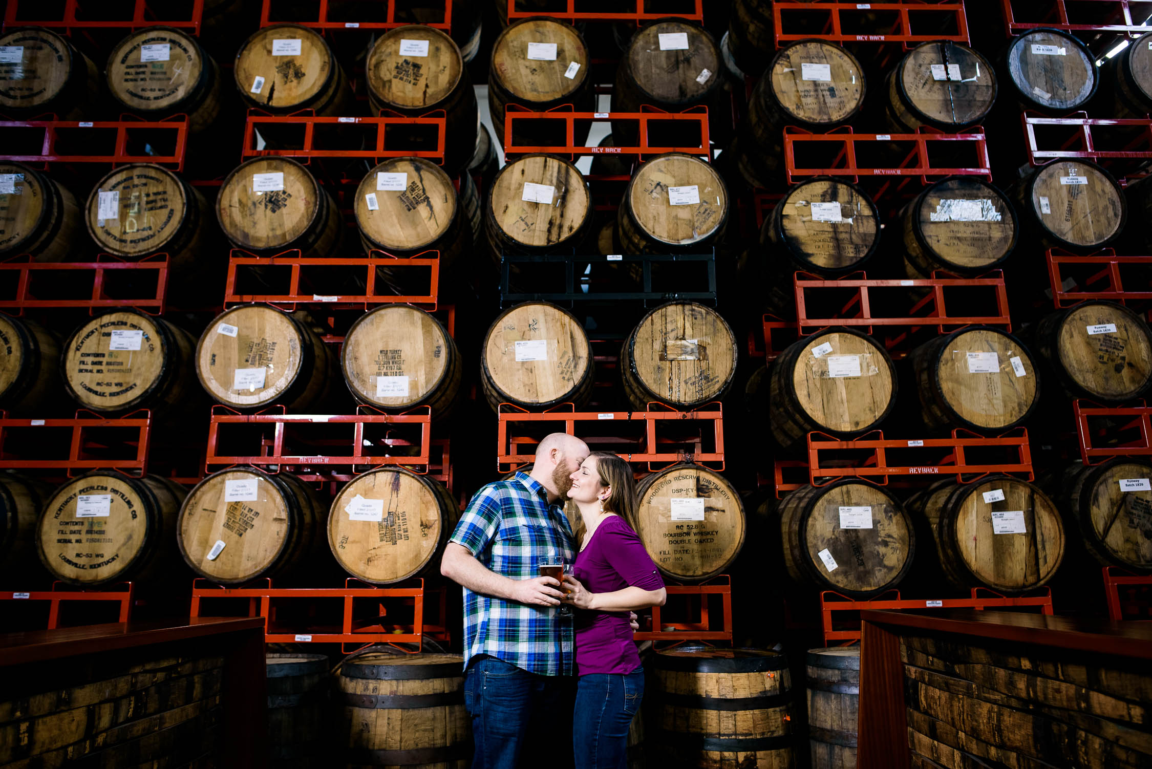 Couple kisses in front of aging barrels at Revolution Brewing during their Chicago engagement session.