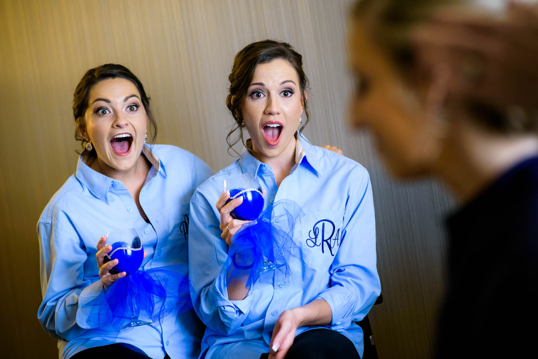 Bridesmaids react to the bride getting ready before a St. Charles Country Club wedding.