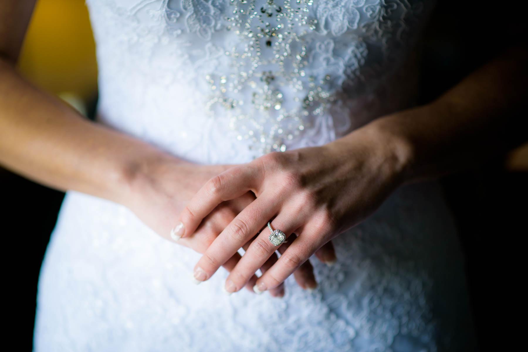 Close up wedding ring and wedding dress detail photo.