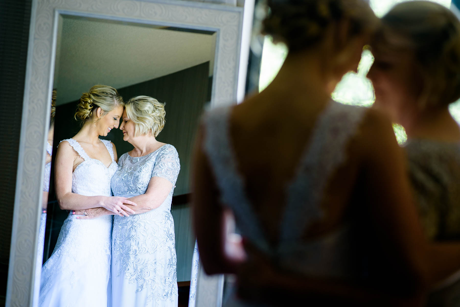 Tender emotional moment between mother and bride before a St. Charles Country Club wedding.