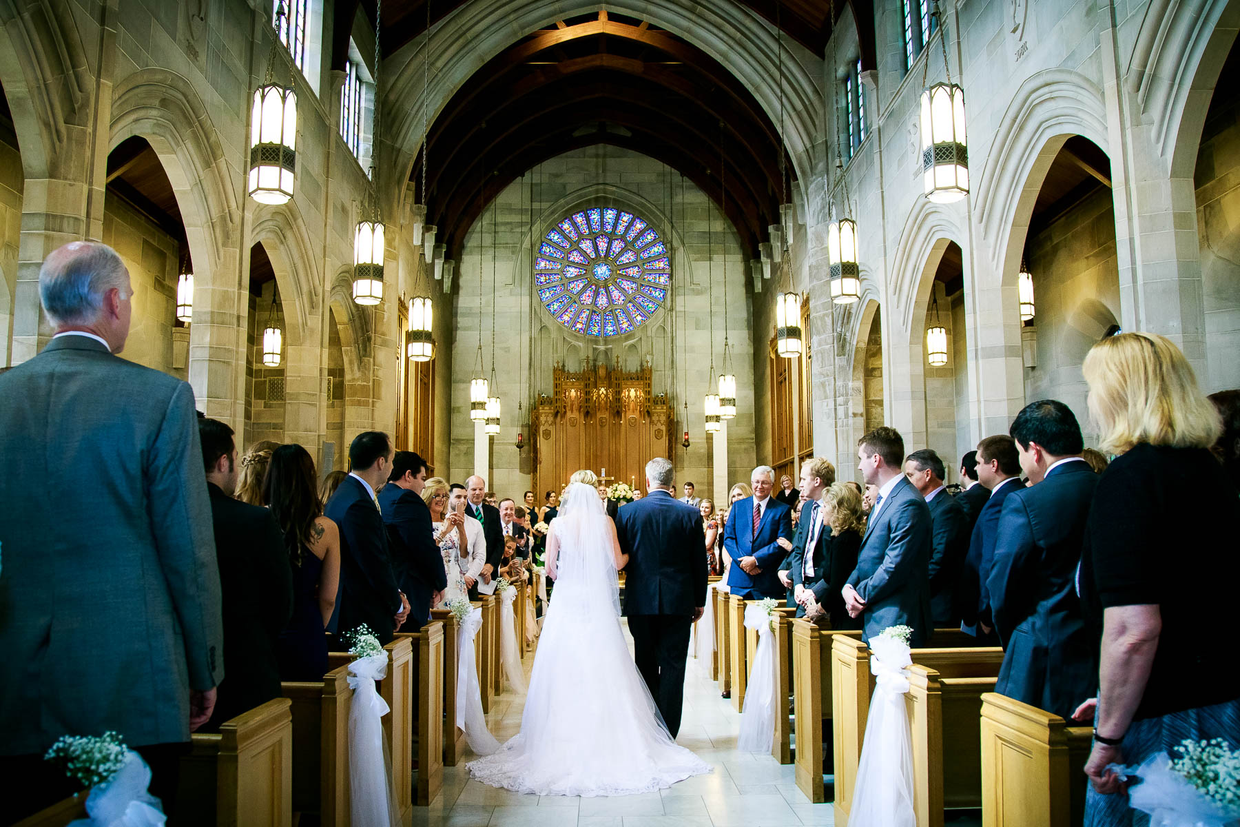 Father and bride walk down the aisle during a wedding ceremony at Baker Memorial United Methodist Church in St. Charles