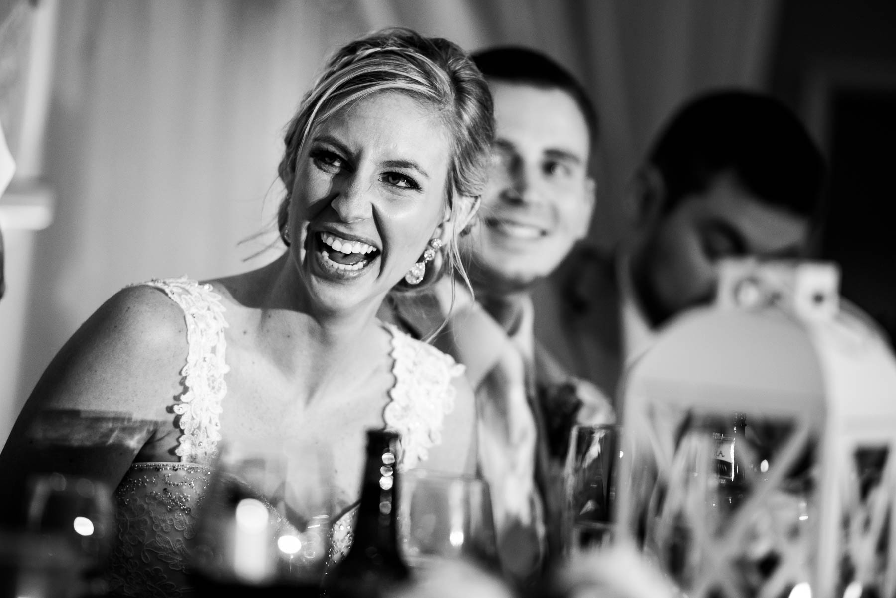 Bride and groom laugh during wedding party speeches at the St. Charles Country Club wedding.