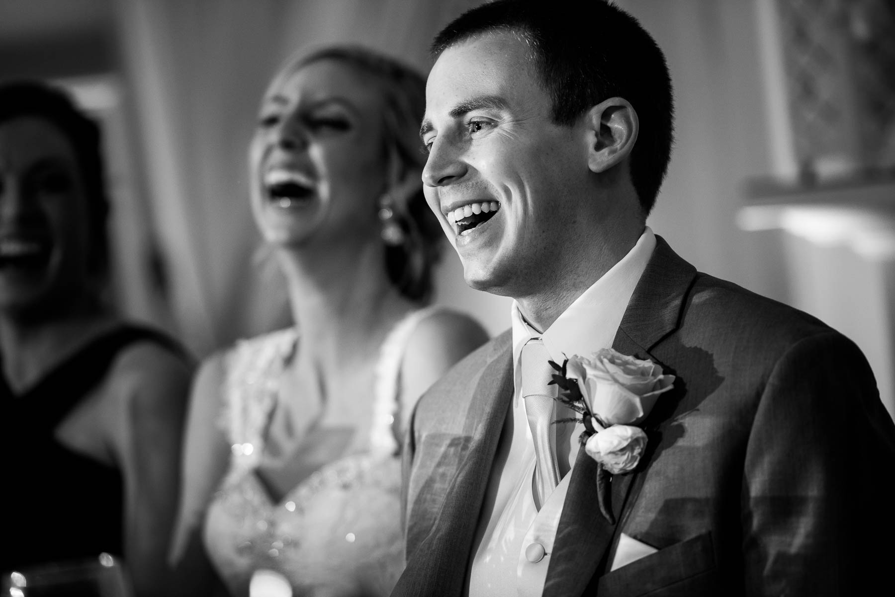 The couple laughs with the best men during their St. Charles Country Club wedding.