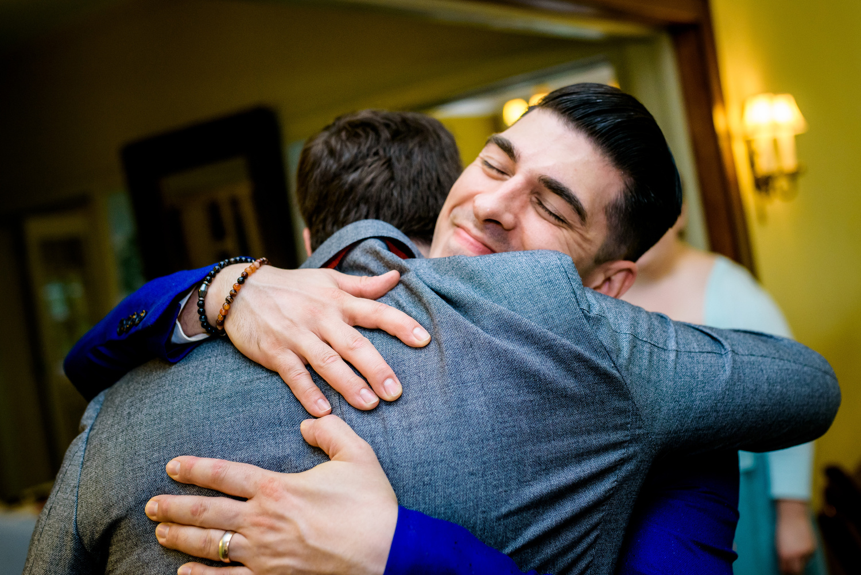 Groom gets a hug during a Cheney Mansion wedding in Oak Park.