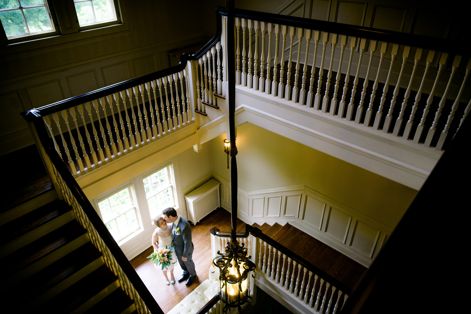 Indoor grand staircase portrait of the couple during a Cheney Mansion wedding in Oak Park.